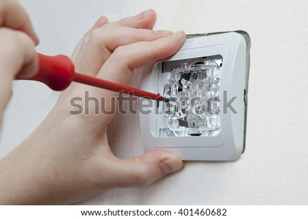 Changing room wall light switch installation with a screwdriver, close-up electrician hands. - stock photo