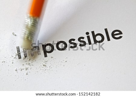 Changing the word impossible to possible with a pencil eraser - stock photo
