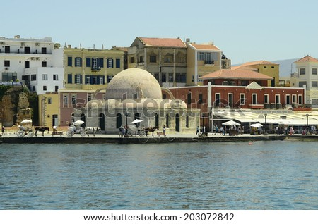 CHANIA, GREECE - MAY 27: Unidentified tourists in the harbor of the city in Crete with Hassan Pascha mosque - aka Janissaries mosque a landmark of the city in Crete, on May 27, 2014 in Chania, Greece
