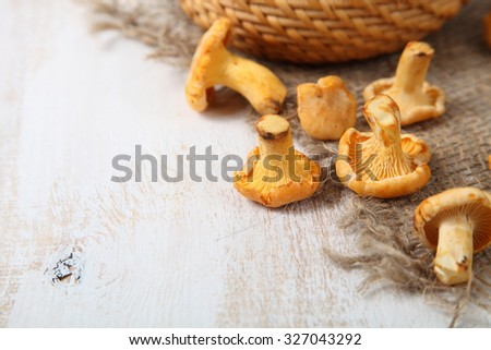 Chanterelles in a basket on a wooden table