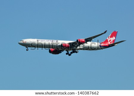 CHANTILLY, VA, USA - SEPTEMBER 24, 2012: Virgin Atlantic Airbus A340 landing at Dulles Airport. Virgin Atlantic is a British airline and part of Sir Richard Branson's Virgin Group. - stock photo