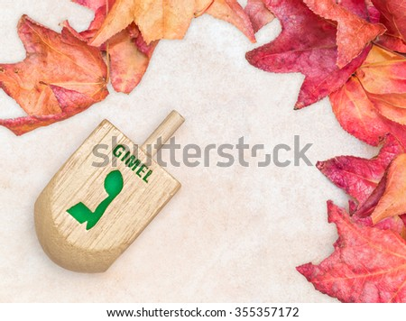 Chanukah dreidel with autumn leaves. Large dreidel with the winning Hebrew letter gimel. Slight drop shadow. Seasonal holiday theme.  - stock photo