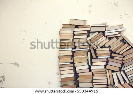 chaotic stack of old books background, selective focus, filter applied