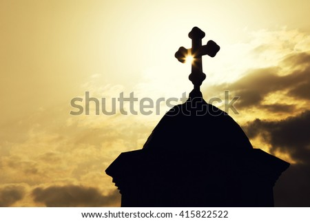 Chapel or church roof with a cross in silhouette against a sunburst at sunrise or sunset in an atmospheric spiritual skyscape. - stock photo