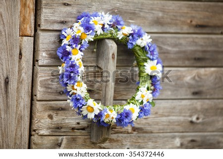 Chaplet from blue cornflowers on the wooden door - stock photo