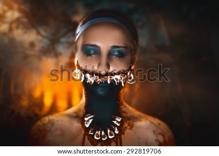 Character with big teeth and black mouth. Professional make up for horror film (faceart, bodyart, aqua grim), cosmetics. Realistic photo. Can be used for Halloween party, vampire saloon, studio horror - stock photo