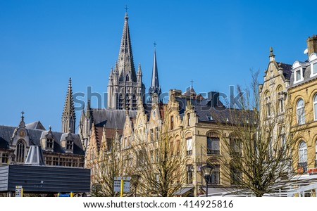 Characteristic Flemish high pitch roof lines in the main square of Ypres (Ieper), Belgium, with the spire of St. Martin's Cathedral in the background - stock photo