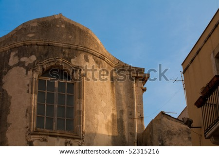 Characteristic windows in a ancient wall of old building - stock photo