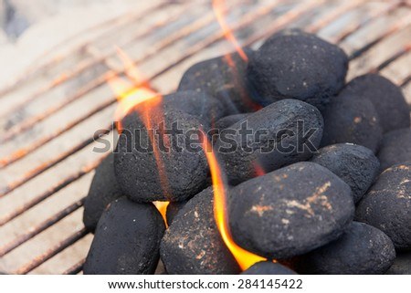 Charcoal briquettes on fire in a BBQ - stock photo