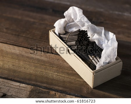 charcoal for sketching in a grey cardboard box on a wooden table - stock photo