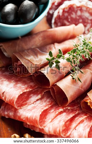 Charcuterie assortment and black olives on wooden background - stock photo