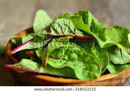 Chard leaves in a wooden bowl.Rustic style. - stock photo