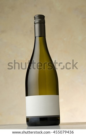 Chardonnay wine bottle with blank label sitting on stone surface