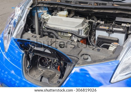 Charge port and motor unit under the hood of an electric car - stock photo