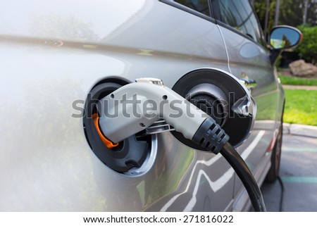 Charging an electric car on a  parking lot - stock photo