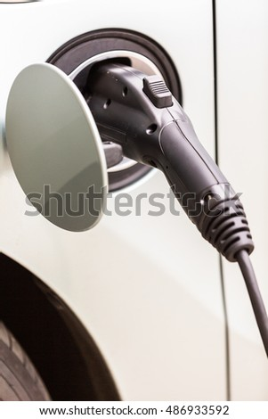 Charging electric car in residential garage.