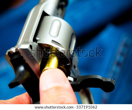 Charging the drum of revolver, close up - stock photo