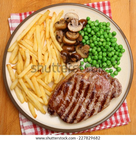 Chargrilled sirloin steak dinner with fries, mushrooms and peas. - stock photo