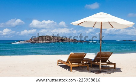 Charis and umbrella at a pristine beach in Mexico. - stock photo