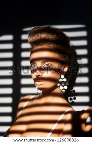 Charisma. Charming Woman's Face in Shadow of Roller Blind - stock photo