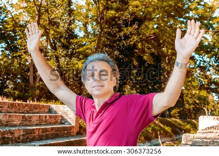 Charismatic and handsome Caucasian sportsman of forty with grey hair wearing red polo shirt and dark linen trousers is raising arms while sitting on the steps of Mill Canal in Emilia Romagna in Italy - stock photo
