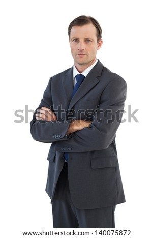 Charismatic businessman standing with arms crossed on white background - stock photo