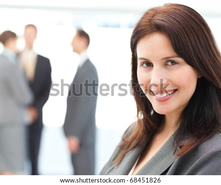 Charismatic businesswoman posing in front of her team while talking on the background