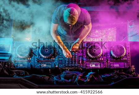 Charismatic disc jockey at the turntable. DJ plays on the best, famous CD players at nightclub during party. EDM, party concept. - stock photo