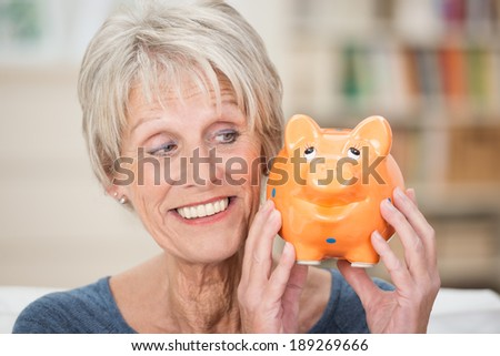 Charismatic elderly woman holding up a piggy bank looking sideways at is as she smiles while contemplating what to do with her savings - stock photo