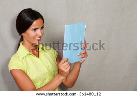 Charismatic lady holding and looking at tablet with toothy smile in green blouse against grey texture background - stock photo