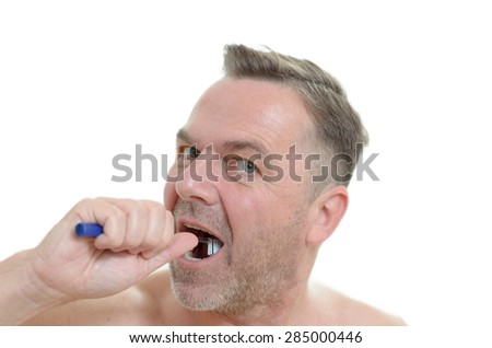 Charismatic man cleaning his teeth looking at the camera with a comic expression with the toothbrush in his mouth