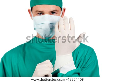 Charismatic surgeon wearing surgical gloves against a white background - stock photo