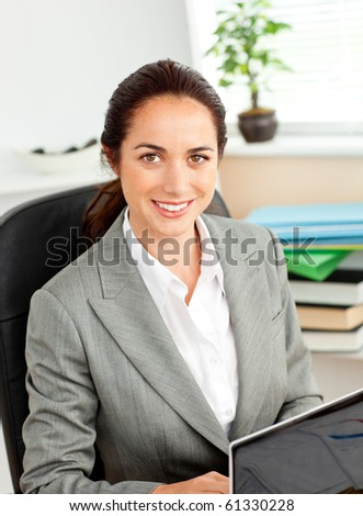 Charismatic young businesswoman using her laptop sitting at her desk in her office - stock photo