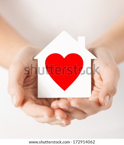 charity, real estate and family home concept - closeup picture of female hands holding white paper house with red heart - stock photo