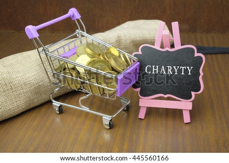 CHARITY word in mini blackboard with gold coins in wooden table. - stock photo