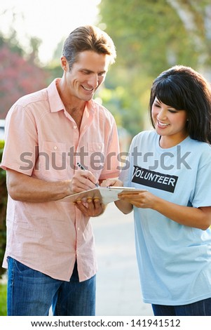 Charity Worker Collecting Sponsorship From Man In Street