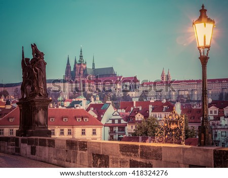 Charles Bridge at sunrise, Prague, Czech Republic. Dramatic statue and view on Prague Castle with St. Vitus Cathedral. Vintage - stock photo