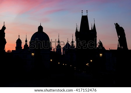 Charles Bridge at sunrise, Prague, Czech Republic. Dramatic statues and medieval towers. Silhouettes at dawn - stock photo
