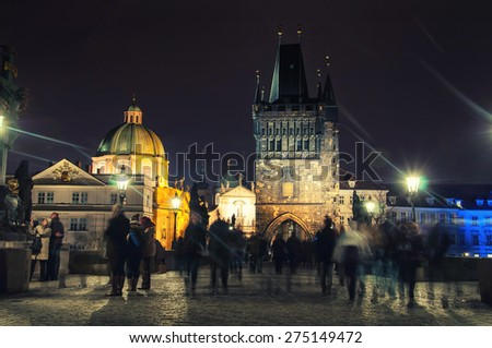 Charles bridge in Prague, Czech Republic at night with blurred people. Lens flare, street lamps light and illumination - stock photo