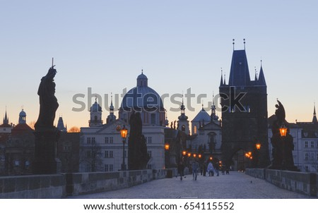 Charles bridge,  twilight scenery, street lights visible. Prague iconic travel destination, Czech Republic.