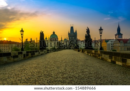 Charles bridge with its statuette and the roofs of the building from Old Town, in Prague during the sunrise, Bohemia, Czech Republic - stock photo