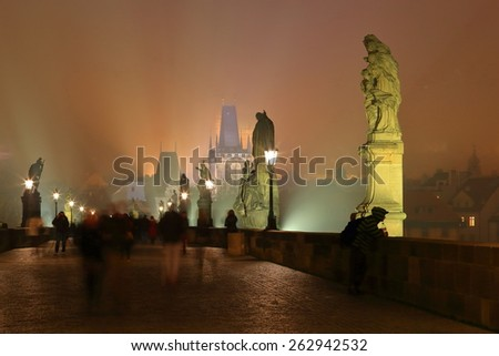 Charles bridge with tall sculptures surrounded by fog at night, Prague, Czech Republic - stock photo