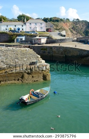 Charlestown Harbour entrance and quay with small boat. Cornwall. England - stock photo