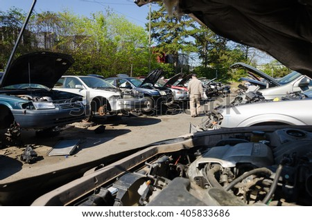 Charlotte, NC, United States - April 14, 2016: Man looking for car parts on a junk yard in a sunny day