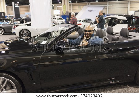 CHARLOTTE, NC, USA - November 11, 2015: Visitor enjoying a BMW on display during the 2015 Charlotte International Auto Show at the Charlotte Convention Center in downtown Charlotte.