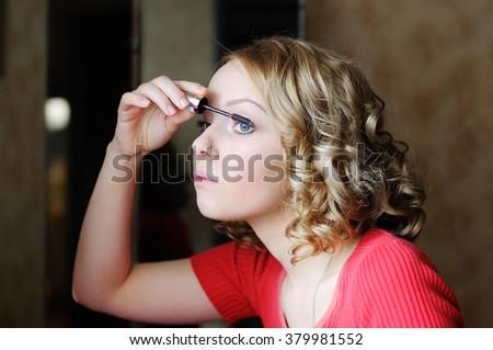 Charming adolescence girl applying mascara  - stock photo