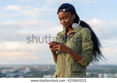 Charming african american girl listen to music and relaxing. Smiling young black lady on blurred city background - stock photo