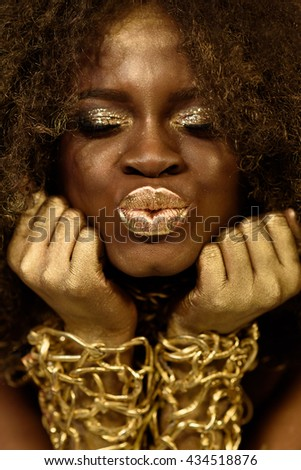 Charming african american model wearing gold accessoaries, makeup and curly hair making kiss lips, closed eyes - stock photo