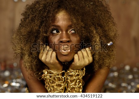 Charming african american model wearing gold accessoaries, makeup and curly hair making kiss lips for camera - stock photo