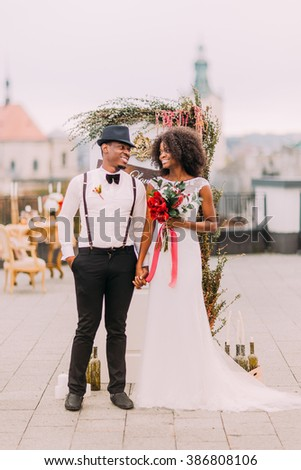 Charming african newlyweds dreamily looks on each other. Wedding day. Rooftop. Lviv architecture on background - stock photo